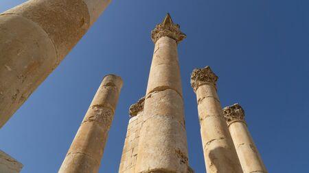 Tall columns of ancient Temple of Zeus situated behind walls of Greco-Roman settlement of Gerasa, Jerash, Jordan
