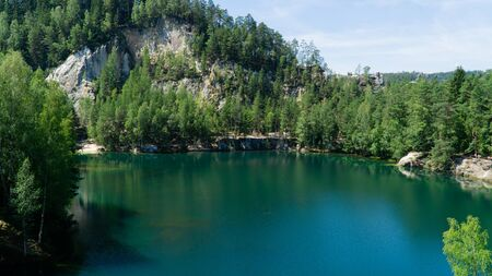 Flooded sandpit in Adrspach Rocks, lake with beautiful clear turquoise water hidden in the middle of forest, Czech Republic