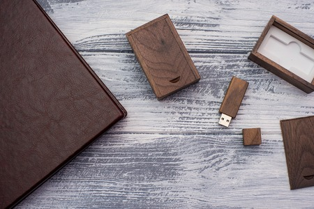 Wooden flash drive, leather book, light wooden background