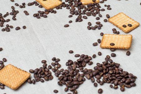 The background of a gray cloth made of old and coarse burlap, on which lies a certain amount of brown coffee beans with a yellow rectangular biscuit Фото со стока
