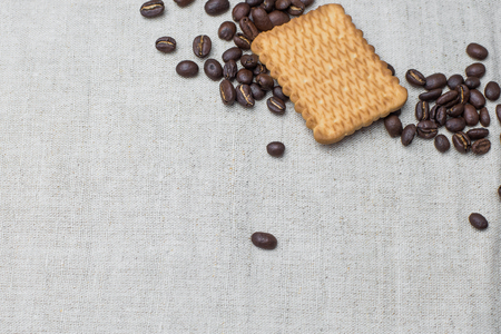 The background of a gray cloth made of old and coarse burlap, on which lies a certain amount of brown coffee beans with a yellow rectangular biscuit Stock Photo