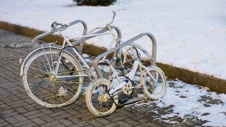 White retro bicycles near a snowdrift