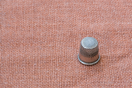 A metal thimble. Close-up, space for text