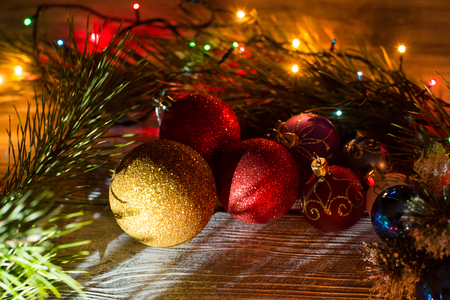 Round New Year garland on a wooden background. Christmas decorations, balls, garlands, spruce, light bulbs