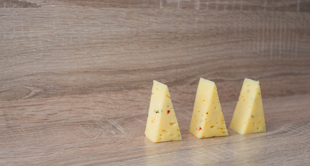 three slices of cheese on a wooden background