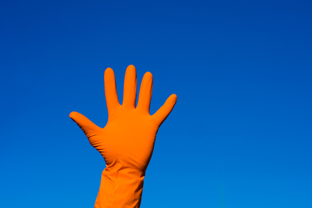 Hand in orazhevoy glove, a gesture against the blue sky.