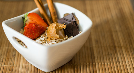 Bowl of oats with strawberry, cinnamon, chocolate and peanut butter Stok Fotoğraf