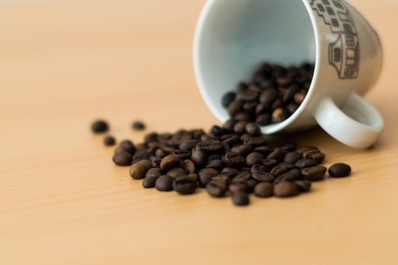 Coffee beans spilled out of a white cup Stok Fotoğraf