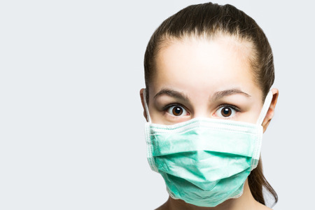 Young girl in doctors mask looking surprised and shocked Stok Fotoğraf