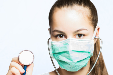 Girl in a doctors mask holding a stethoscope  medical concept