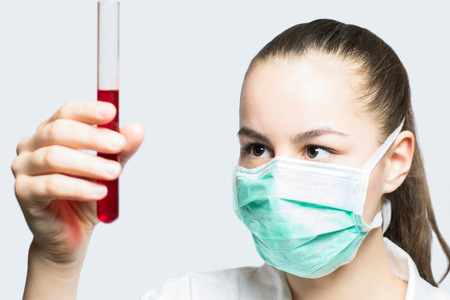 Girl in a mask holding test tube with red liquid  science concept