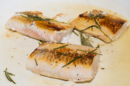 Salmon fillets getting cooked on a pan with rosemary