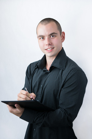 Man holding stack of papers and writing