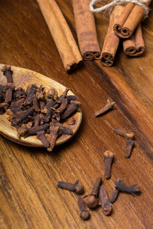 Cloves with cinnamon sticks on a wooden table