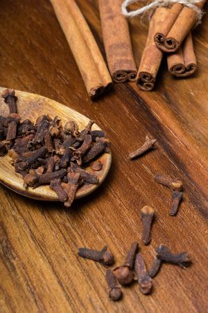 cinnamon sticks: Cloves with cinnamon sticks on a wooden table