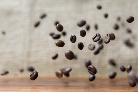 Coffee beans falling down on a wooden plank Stockfoto