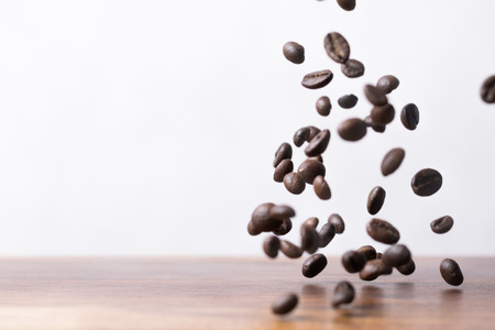Coffee beans falling down on a wooden plank Imagens