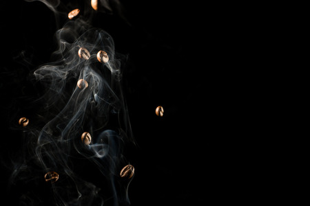 Coffee beans falling down trough smoke over black background - isolated