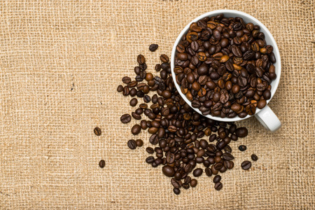 Cup full of coffee beans over cloth background Stok Fotoğraf