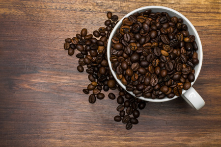Cup full of coffee beans over wooden background