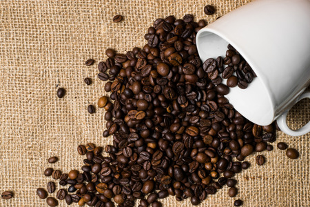 shop tender: Cup full of coffee beans spilled over cloth background