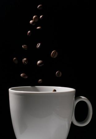 Coffee beans falling in a mug Stok Fotoğraf