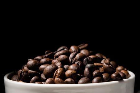 grano de cafe: Taza de café llena de granos de café sobre fondo negro Foto de archivo