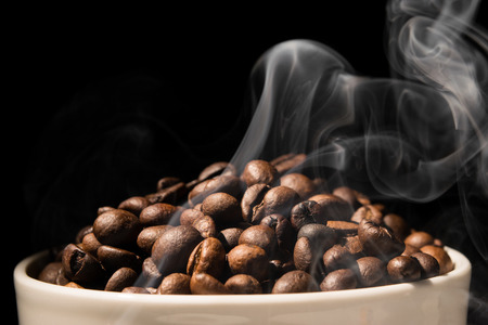 Coffee mug full of coffee beans with smoke Stok Fotoğraf