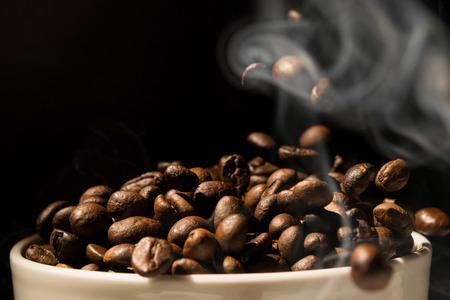 grano de cafe: Taza de café llena de granos de café con el humo