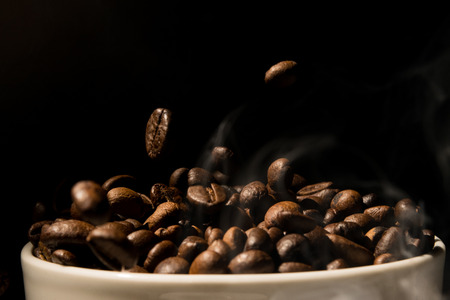shop tender: Coffee mug full of coffee beans with smoke Stock Photo