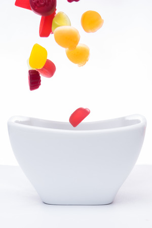 Colorful jelly gum drops falling into a white bowl Stok Fotoğraf