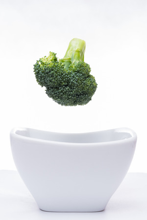 Fresh broccoli falling into a white bowl Imagens