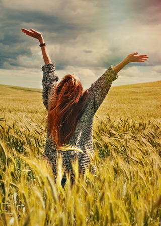 fashion young red hair woman standing back hands up on breathtaking view of dramatic storm sky in the field   Foto de archivo