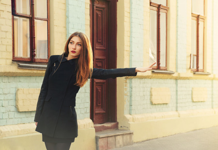 Beautiful elegant young woman on a city street catching a taxi photo