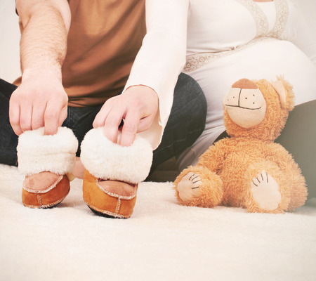 anticipating: hands of pregnant couple with little boots anticipating little baby, concept of newborn