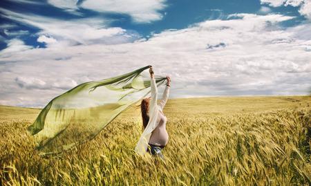 embarazada feliz: Mujer embarazada sintiendo que la libertad de la naturaleza en campo de oro ventoso, embarazo feliz y saludable