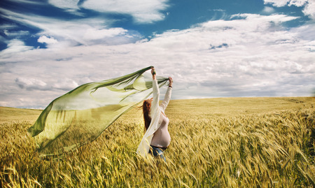 sports field: pregnant woman feeling freedom of nature in windy gold field, happy healthy pregnancy Stock Photo