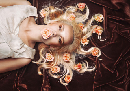 sensual tender woman portrait with magnificent gaze and peachy roses on chocolate background in studio