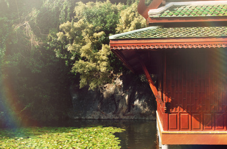 beautiful nature background of traditional chinese house on the lake with koi fish in summer sunny beam photo