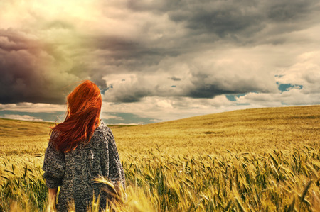 fashion young red hair woman standing back outdoor on breathtaking view of dramatic storm sky in the field   Stock Photo
