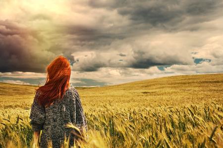 personas de espalda: moda joven mujer de pelo rojo de pie de nuevo al aire libre en vista impresionante del espectacular cielo de tormenta en el campo