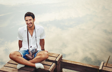 hombres con estilo joven y guapo con cámara de la vendimia de chill out junto al mar en el muelle