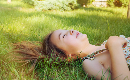 oudoors: happy smiling little girl lying on the grass oudoors in sunny summer day