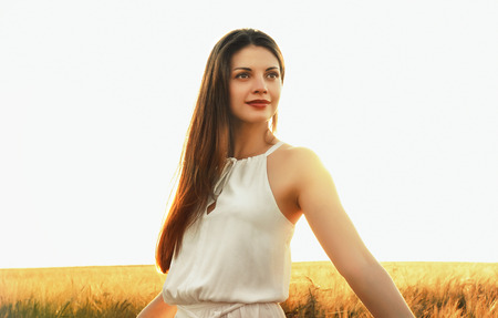 attractive young woman enjoy beautiful nature at the sunset background in the field photo