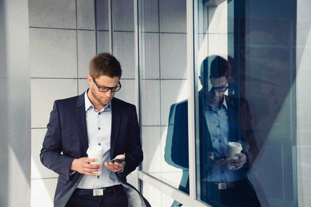man in suit: attractive young businessman with phone device and coffee in hands on office building background