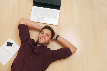 attractive young man relaxing on the wooden floor at home, credit business concept photo