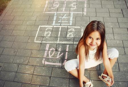 enfant qui joue: belle joyeuse petite fille jouant à la marelle sur aire de jeux à l'extérieur