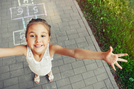 cheerful little girl playing hopscotch on playground outside