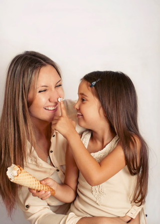 happy family concept: family of mother and daughter having fun with sweet cream puff, happy family concept