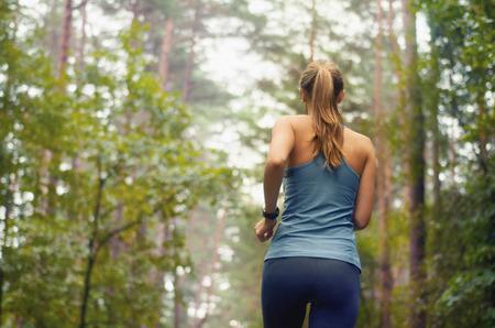 hälsosam livsstil fitness sportig kvinna som kör tidigt på morgonen i skogsområdet, fitness hälsosam livsstilskoncept
